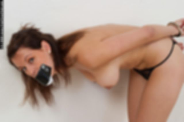 TINDRA HANDCUFFED TOPLESS AND TAPEGAGGED IN THE STUDIO
